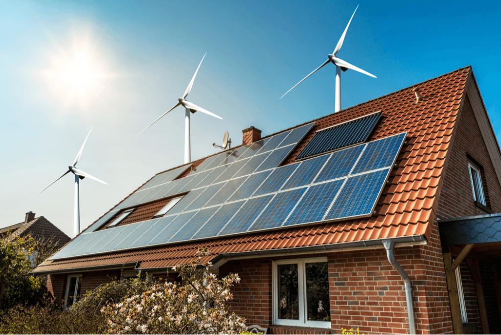 Panel solar en un techo de una casa y turbinas eólicas en torno