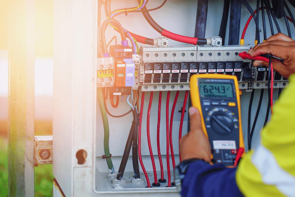 trabajador con multímetro para medir la tensión de los cables eléctricos